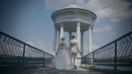 an : Newlyweds go over the bridge. Bride and groom holding hands. Lovers on the background of the white arches and blue sky. Filming with a slider
