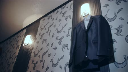 brown dress : Costume hanging on a hanger in the room. Mens Clothing in the interior. Trendy costume. Business style . Business meeting, preparation for it . Businessman prepared suit to a business meeting . Expensive suit to the beautiful interior . Stock Footage