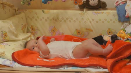 kisbaba : Newborn baby playing with hands and feet lying on her back. Infant up to 2 months and watching plays than that in his crib. Stock mozgókép