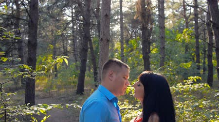 csókolózás : the guy kisses the girl in the woods. romantic date in nature. sincere feelings of two loving people