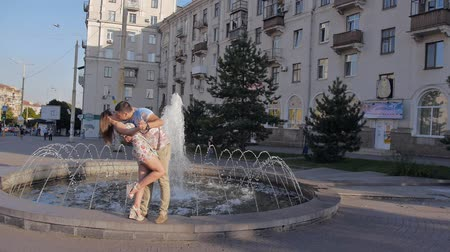 amantes : the lovers by the fountain. Dating couple near the water. Guy hugging a girl. happy young people