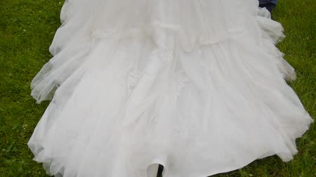 uzun : train wedding dresses. The bride walking on the grass. Train on the road Stok Video