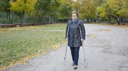 инвалидность : a woman with a foot injury walking through the park on crutches