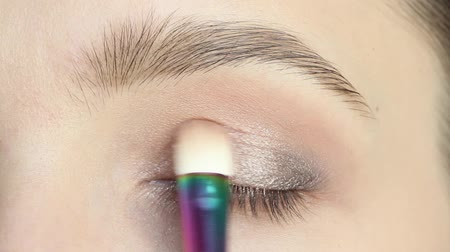 pigmento : Closeup portrait of woman applying eyeshadows using makeup brush