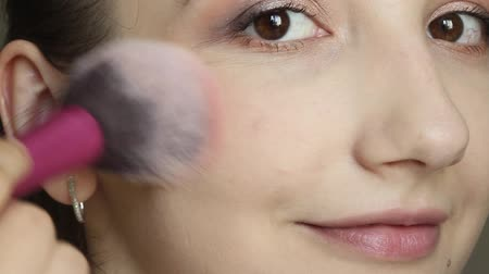 Closeup portrait of woman applying blush using makeup brush 動画素材