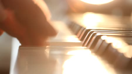 fortepian : Mans hands playing electrical piano in the morning. Pleasant sunshine light from a window indoors.