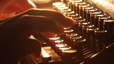 máquina de escrever : Close up shot of man typing on old vintage retro typewriter; backlit news, media or communication concept