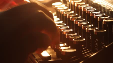 Close up shot of man typing on old vintage retro typewriter; backlit news, media or communication concept