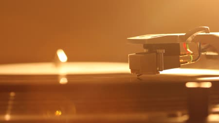 gramophone : Close up of turntable needle on a vinyl record. Turntable playing vinyl. Needle on rotating black vinyl. Backlight Stock Footage