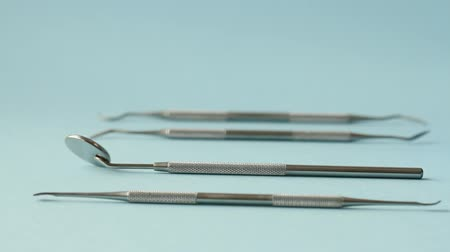 угловой : Dentist choose or rearrange set of dentist tools on blue background: Dental Hygiene and Health conceptual image Стоковые видеозаписи