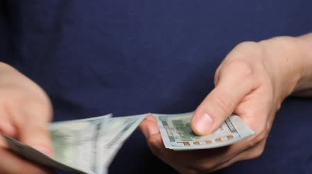 durgunluk : Caucasian hands counting dollar banknotes on darl blue background. Savings, finances, economy and home concept