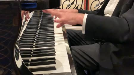 zongora : Mature male pianist in black suit and classic shirt plays beautiful black grand piano. Close up view