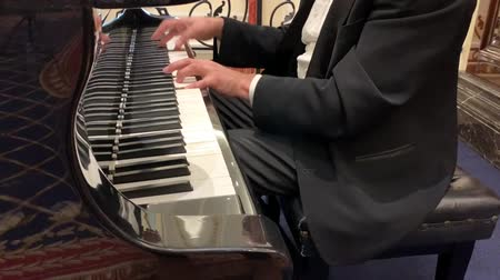 Mature male pianist in black suit and classic shirt plays beautiful black grand piano. Close up view