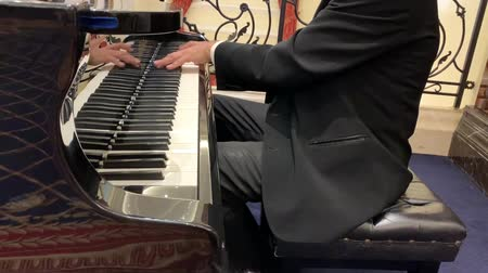 classical suit : Mature male pianist in black suit and classic shirt plays beautiful black grand piano. Close up view