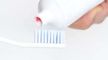 szorítás : Putting toothpaste on a brush on white background Stock mozgókép