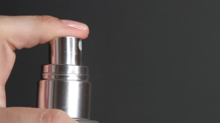 dezodorant : Closeup of spraying perfume or thermal water glass bottle. Finger pushing pump of cosmetic bottle on a black background. Wideo