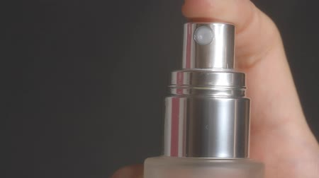 sprayer : Closeup of spraying perfume or thermal water glass bottle. Finger pushing pump of cosmetic bottle on a black background. Stock Footage