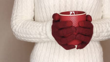 knitted : Young woman in white sweater is holding red cup of tea or coffee. Changing hand, trying to warm hands with hot drink