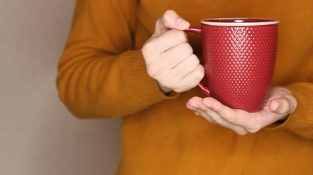 knitted gloves : Young woman in yellow sweater is holding red cup of tea or coffee. Changing hand, trying to warm hands with hot drink Stock Footage