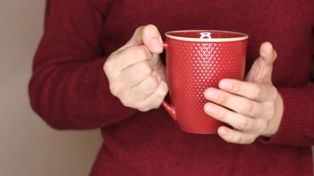 knitted gloves : Young woman in red sweater is holding red cup of tea or coffee. Changing hand, trying to warm hands with hot drink