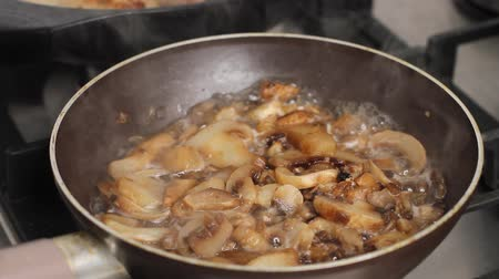 gombák : Mushrooms being cooked in frying pan in kitchen, delicious dish in olive oil and sauce