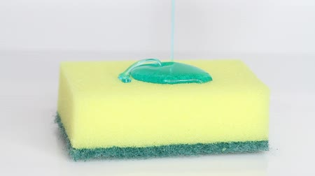 моющее средство : Blue dish washing liquid gel is pouring on yellow sponge on white background