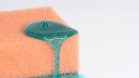 ワッシャー : Blue dish washing liquid gel is pouring on orange sponge on white background