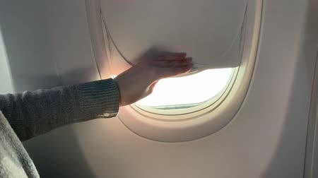 woman hand is opening window of airplane. Clouds and sky as seen through window of an aircraft, air plane.