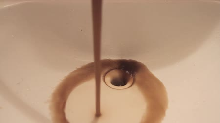 Close up dirty rusty brown polluted water flowing from tap in bathroom sink. Vídeos