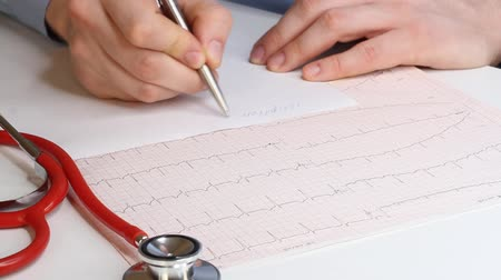 zavřít : Cardiologist looks at the cardiogram and prescribes the prescription to the pharmacy. Fennedoscope, stethoscope and cardiogram. Healthcare and early diagnosis concept.