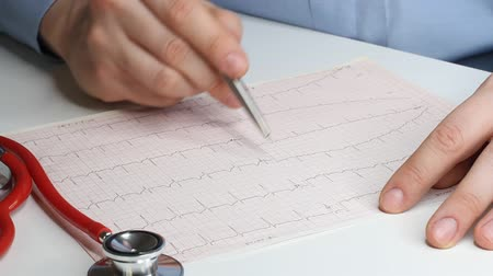 Cardiologist looks at the cardiogram and prescribes the prescription to the pharmacy. Fennedoscope, stethoscope and cardiogram. Healthcare and early diagnosis concept.