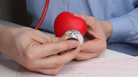 Cardiologist doctor checks heart rate on a toy red heart. Phonendoscope, stethoscope and cardiogram. Healthcare and early diagnosis concept.