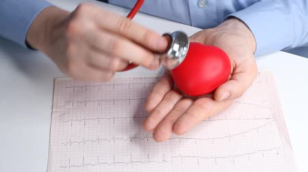 examinar : Cardiologist doctor checks heart rate on a toy red heart. Phonendoscope, stethoscope and cardiogram. Healthcare and early diagnosis concept.