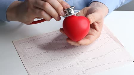 ambulância : Cardiologist doctor checks heart rate on a toy red heart. Phonendoscope, stethoscope and cardiogram. Healthcare and early diagnosis concept.