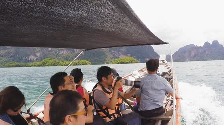 surat : SURAT THANI, THAILAND - 12 SEPTEMBER 2015 - Unidentified tourists travel on traditional Thai longtail boat for sightseeing in Cheow Lan reservoir in Surat Thani province, Thailand. Stock Footage