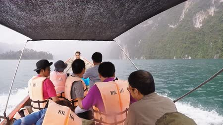 SURAT THANI, THAILAND - 12 SEPTEMBER 2015 - Unidentified tourists travel on traditional Thai longtail boat while it is raining ahead in Cheow Lan reservoir in Surat Thani province, Thailand.