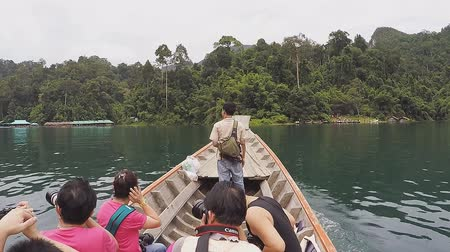 SURAT THANI, THAILAND - 12 SEPTEMBER 2015 - Unidentified tourists travel on traditional Thai longtail boat in Cheow Lan reservoir in Surat Thani province, Thailand. 影像素材