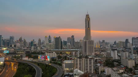 BANGKOK, THAILAND - 16 APRIL 2016 - Time lapse of Bangkok high-rise buildings and traffic light trails on expressway at dusk.