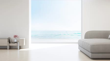 relaks : Sea view living room of luxury summer beach house with glass window and wooden floor. Empty white concrete wall background in vacation home or holiday villa. Hotel interior 3d illustration. Wideo