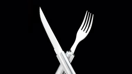 bıçak : knife and fork crossed and rotating in a seamless loop on a black background Stok Video
