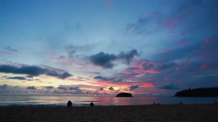 refletir : beautiful sunset behind Pu island at Kata beach Phuket. a lot of tourists relax on the beach during sunset.