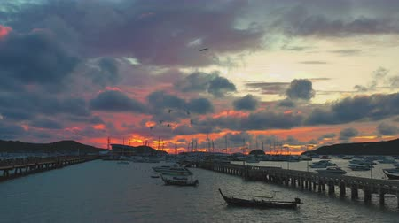 resolution : beautiful sunrise through the mountain in Chalong gulf Chalong gulf is the most important place for marina and port for transport there have two piers amazing red sky above the ocean in the morning