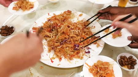 kínai evőpálcikák : A group of people mixing and tossing Yee Sang dish with chop sticks. Yee Sang is a popular delicacy taken during Chinese New Year, believed to bring good fortune and luck Stock mozgókép