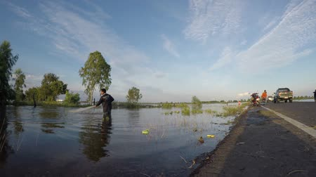 Fishermen casting for fish in the flood season. Stok Video
