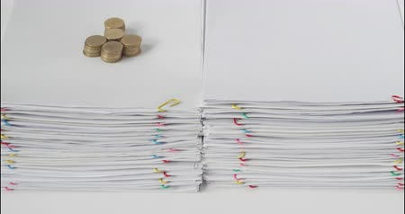 információ : Pile paperwork of report have blur pile of gold coins with spectacles and pencil place on white table time lapse.