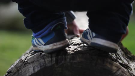 A child tries to walk on a log