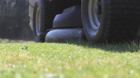 A lawn mower approaches camera and drives past.  Shot angles included Vídeos