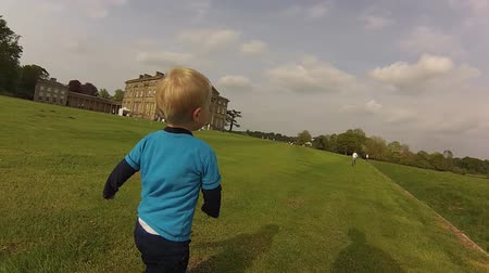 A boy runs on the grounds of a stately home Vídeos