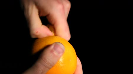 Close up of an orange being peeled