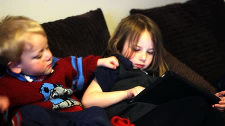 Two children play on a tablet together at home Vídeos